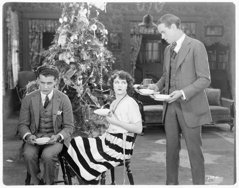 Deux hommes et une femme s'apprêtant à manger le dessert devant le sapin de Noël
