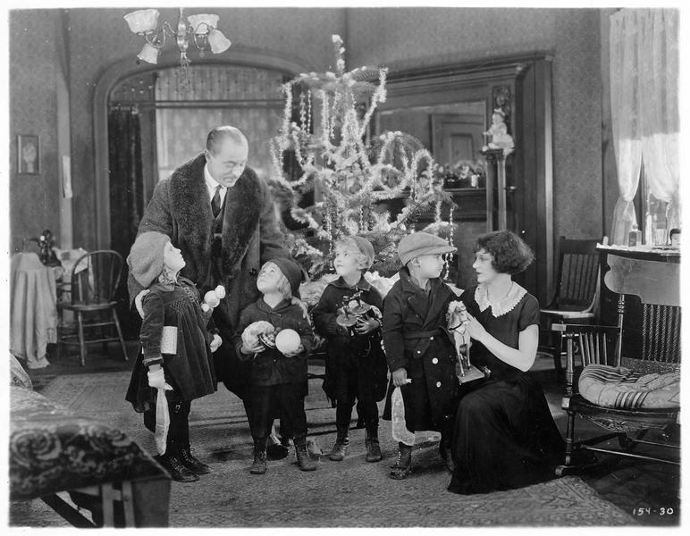 Ann Clemance (V. Dana) avec des enfants devant le sapin de Noël