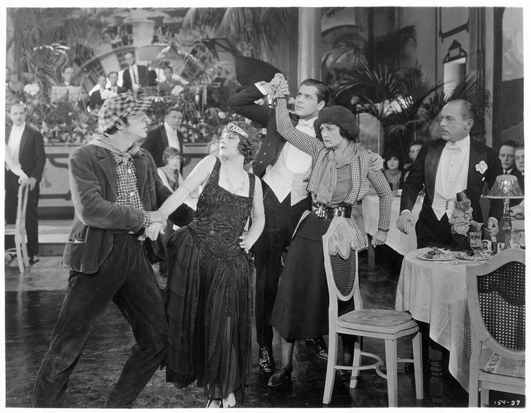 Adrian Torrens (W. Baxter) empêchant Jeanne (R. Theby) de poignarder Ann Clemance (V. Dana) lors d'une soirée