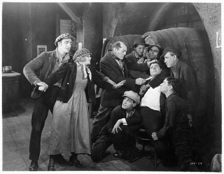 Adrian Torrens (W. Baxter) pris en otage par un groupe d'hommes devant Ann Clemance (V. Dana)