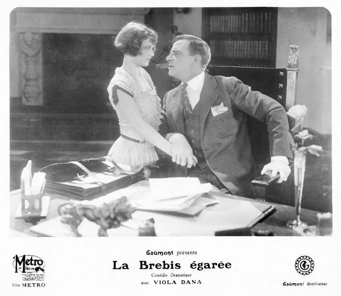 Un homme assis à son bureau et saisissant la main d'une jeune femme (V. Dana)