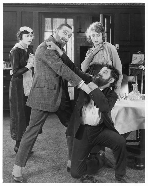 Richard Hatton-Olwell (R. Julian) se battant avec un homme sous le regard effrayé de Winifred Olwell (J. Novak) et de la domestique