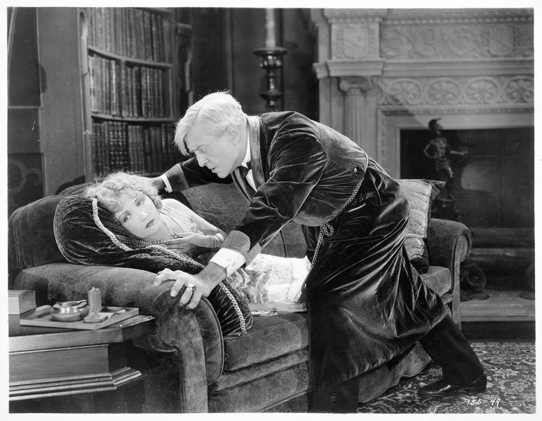 M. Moore (H. Bosworth) se penchant sur Joy Moore (E. Novak), étendue sur le canapé