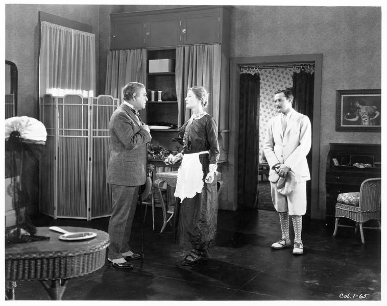 Une domestique (J. Novak) s'adressant à un homme (R. Edison)
