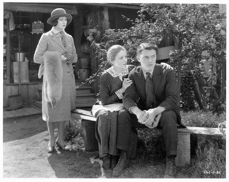 La domestique (J. Novak) prenant un homme (R. Armstrong) par les épaules
