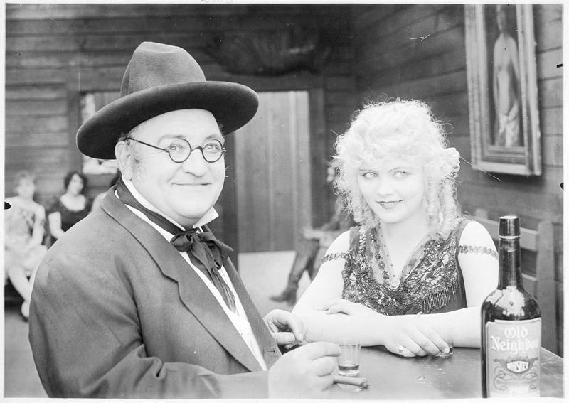 Une jeune femme (W. Westover) et un homme buvant un verre au comptoir