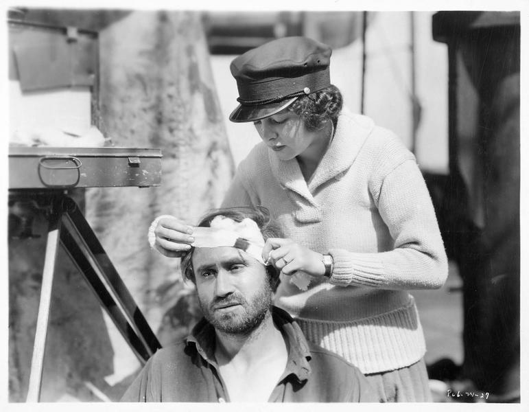 Billie Dove soignant la plaie d'un homme blessé à la tête