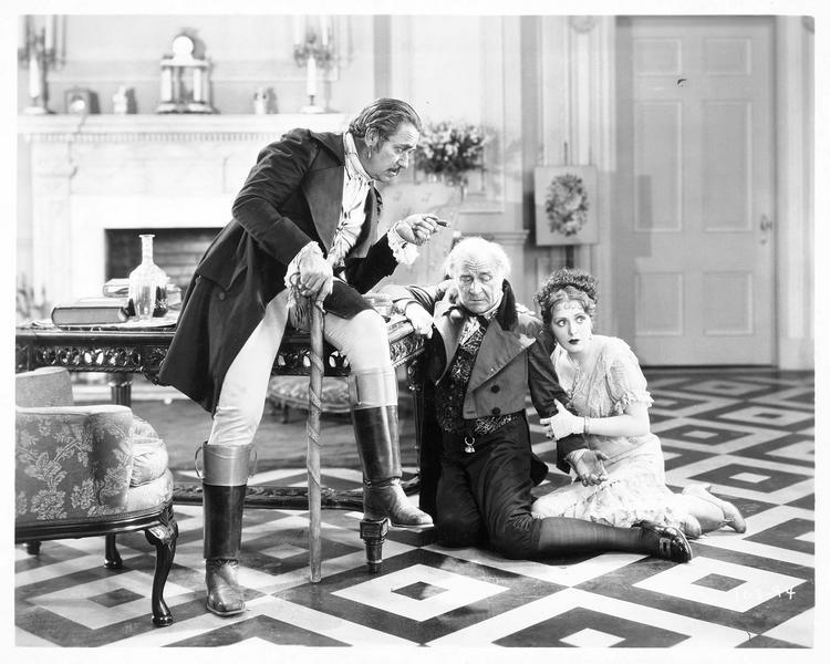 Le capitaine Remy (N. Beery) s'adressant à Louis Frobelle (E. Chautard) et Antoinette Frobelle (B. Dove)