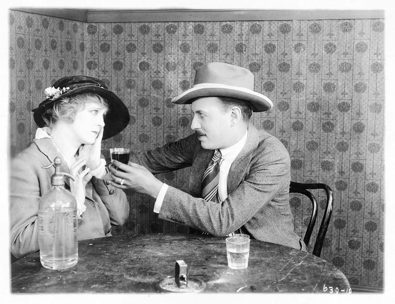Un homme tendant un verre à Mollie Vaughn (B. Bennett)