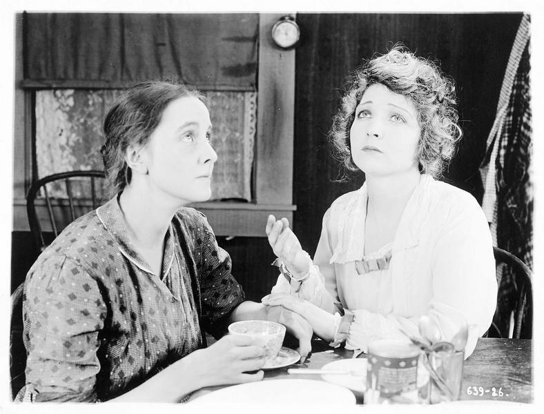 Mollie Vaughn (B. Bennett) et une femme, devant un café, lèvent les yeux au ciel