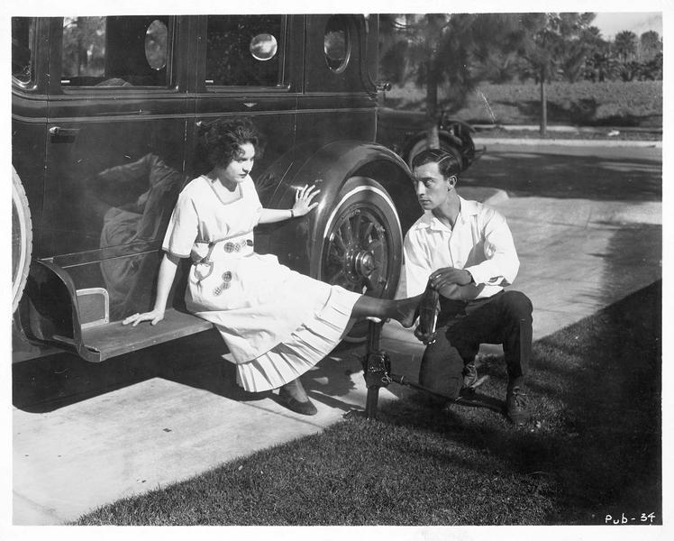 Buster Keaton montrant comment remettre une chaussure au pied d'une femme. Alice Lake servant de cobaye pour la démonstration