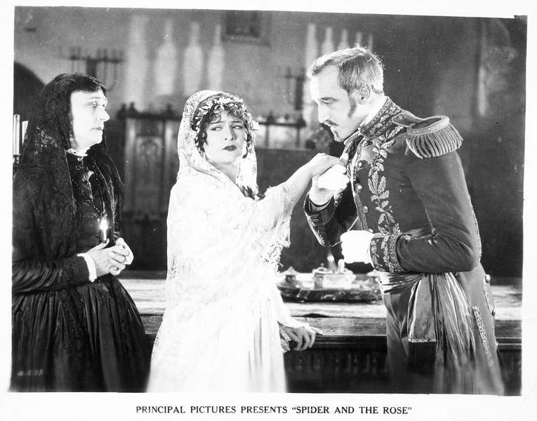 Paula (A. Lake) détournant la tête lorsque Don Fernando (F. Campeau) lui baise la main