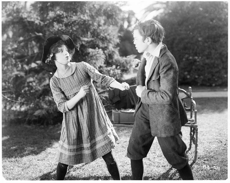 Jane Day (S. Mason) se battant avec un jeune garçon dans un parc de la ville