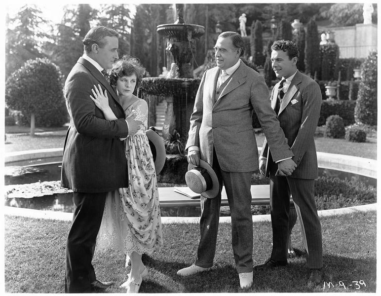 Jenny (S. Mason), Larry Hard (R. MacKee) et deux autres personnages devant la fontaine d'un parc