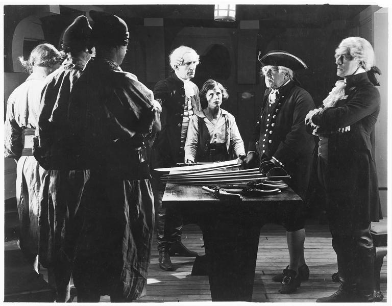 Jim Hawkins (S. Mason) et des notables réunis autour d'une table