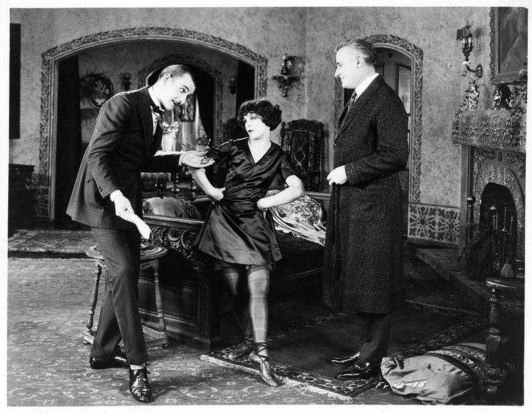Della Marvin (S. Mason) entourée de deux hommes dans un salon