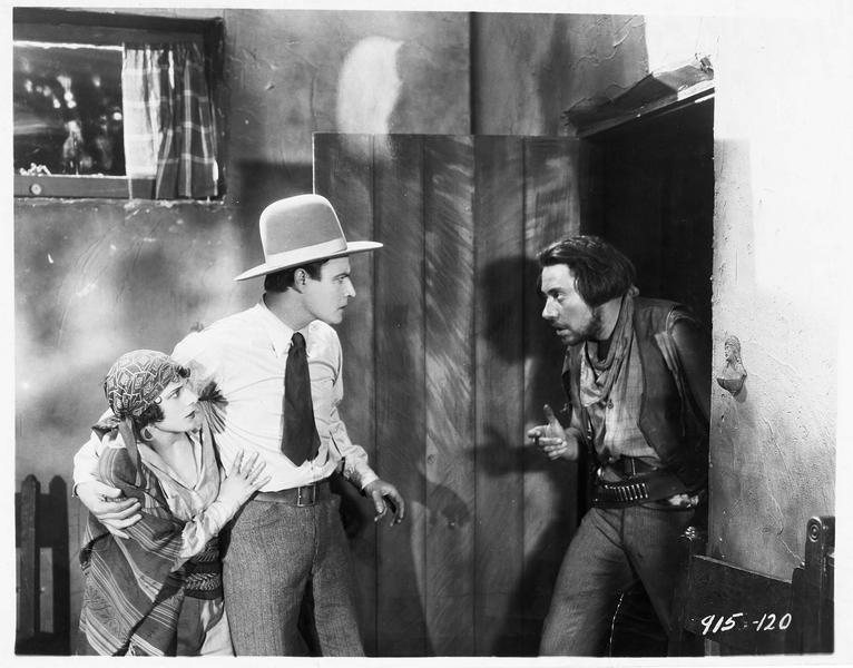 Un homme faisant irruption dans la pièce où se trouvent Mercedes Castanada (S. Mason) et George Thorne (N. Hamilton)
