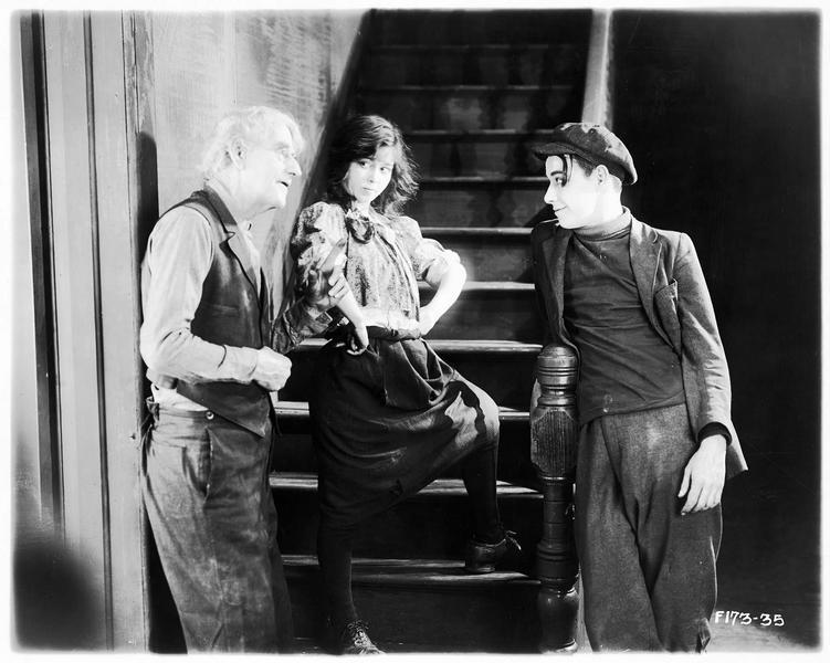 Susie (A. Pennington) au pied de l'escalier écoutant un vieil homme s'adresser à un jeune homme.