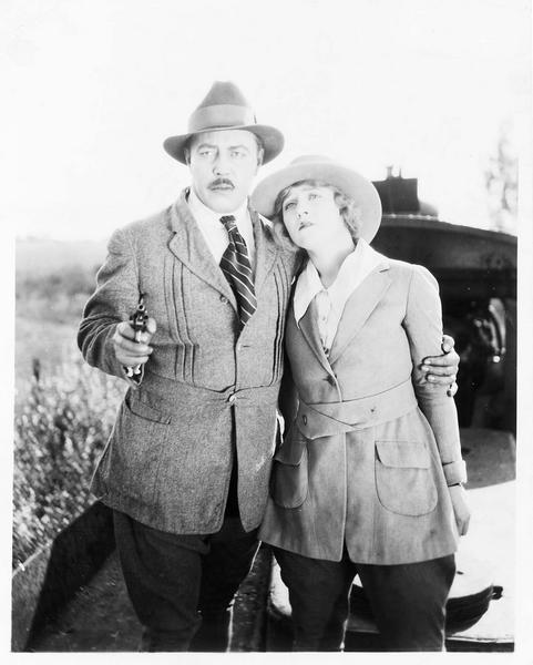 Un homme (W. Oland) braquant un revolver et enserrant une femme (E. Percy) par les épaules