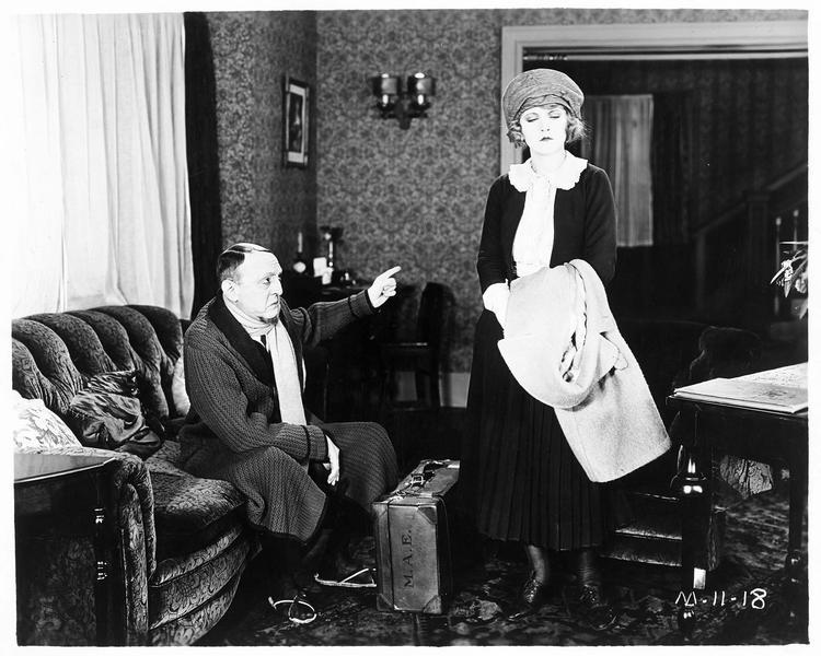 Un homme mettant en garde Mary Emerson (E. Percy) qui s'apprête à partir avec sa valise