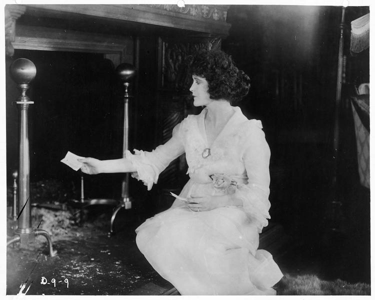 Mrs. John Cleveland (V. Rich) devant la cheminée