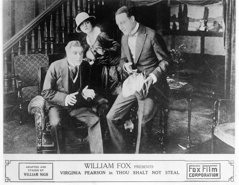 Mary Bruce (V. Pearson), Henry Bruce (E. Mayne) et un troisième personnage dans le salon