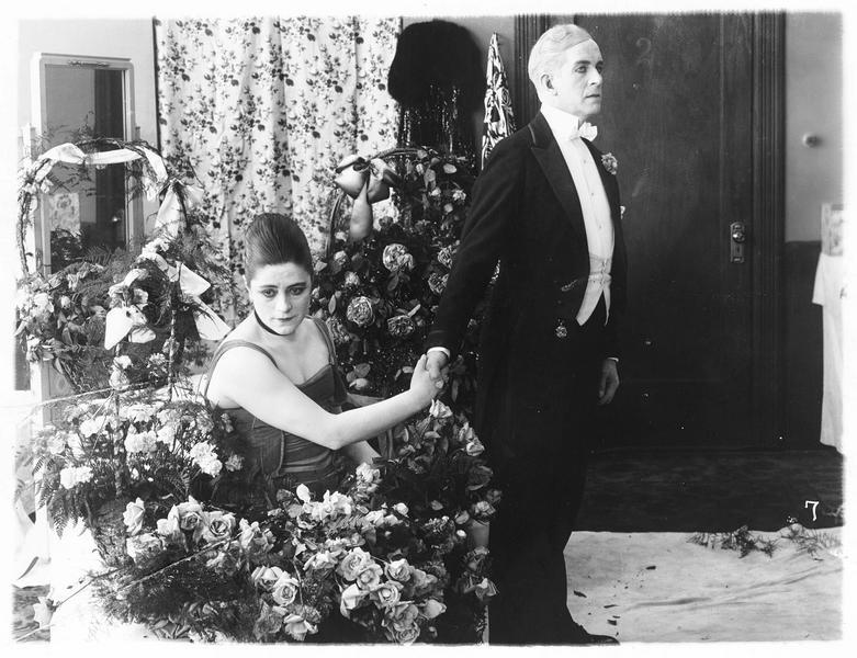 Grace Leonard (V. Suratt) et un homme se tenant la main sans se regarder