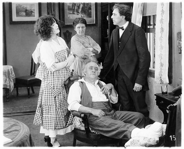 Emma Rolfe (V. Suratt) et deux autres personnages aux côtés d'un homme blessé au pied