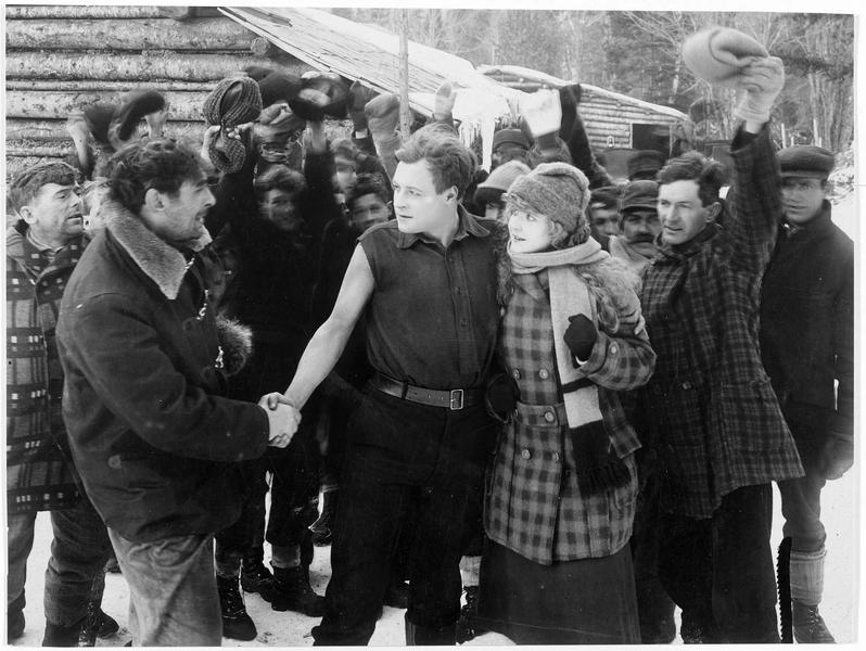 Un homme (H. Lockwood) accompagné d'une jeune femme (A. May) est remercié par une poignée de main