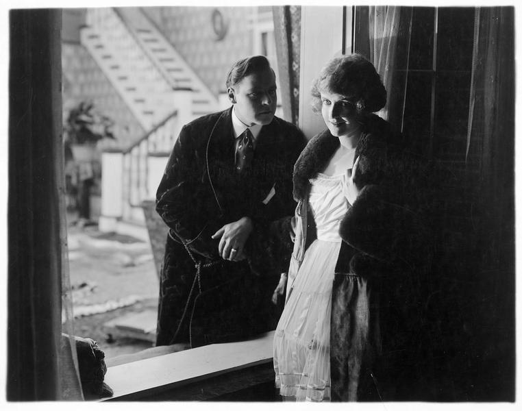 Un homme (H. Lockwood) et une jeune femme (A. May) se parlant à la fenêtre