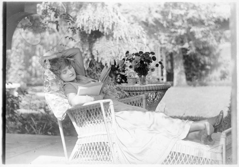 Muriel Main (L. Blake) lisant dans le jardin