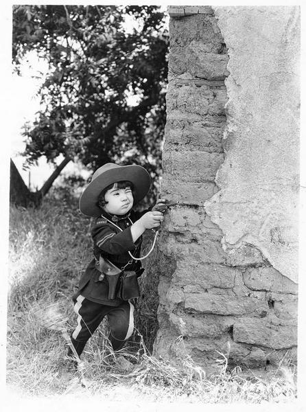 Une fillette (B. Peggy) en tenue de policier visant avec un revolver