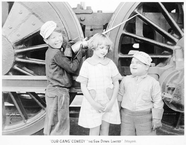 Trois enfants de la troupe 'Our Gang Comedy' devant les roues d'un camion de pompiers