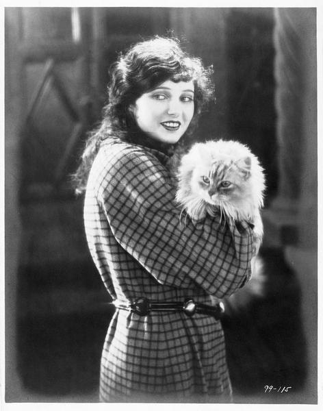 Valerie West (C. Griffith) portant un chat dans les bras