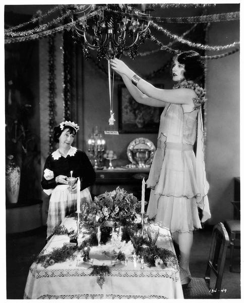 Miriam (C. Griffith) décorant la salle à manger pour la nouvelle année en compagnie de la domestique Mrs. O'Brien (P. O'Bryne)