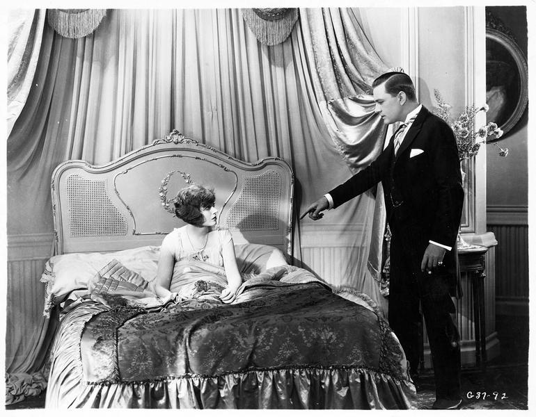 Un homme (K. Harlan) portant un doigt accusateur sur une femme (C. Griffith) assise dans son lit