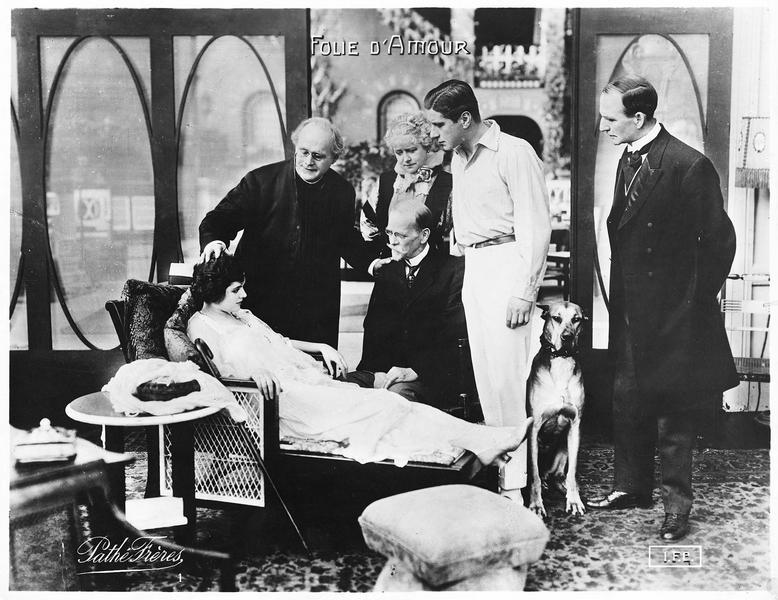 Clarice (E. Hammerstein) semi-allongée sur un divan et entourée de personnes attentionnées, parmi lesquelles le jeune Robert Hyde (R. Warwick)