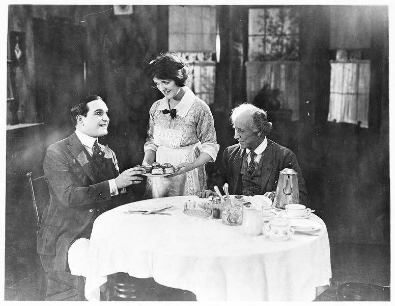 Betty Graham (J. Paige) servant des pâtisseries à Nathaniel Dunham (E. Williams)