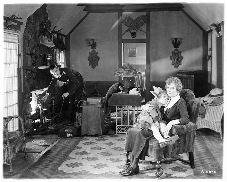 Ogden Fenn (N. Kerry) devant la cheminée et Diana Manneers (M. MacLaren) avec une fillette dans les bras