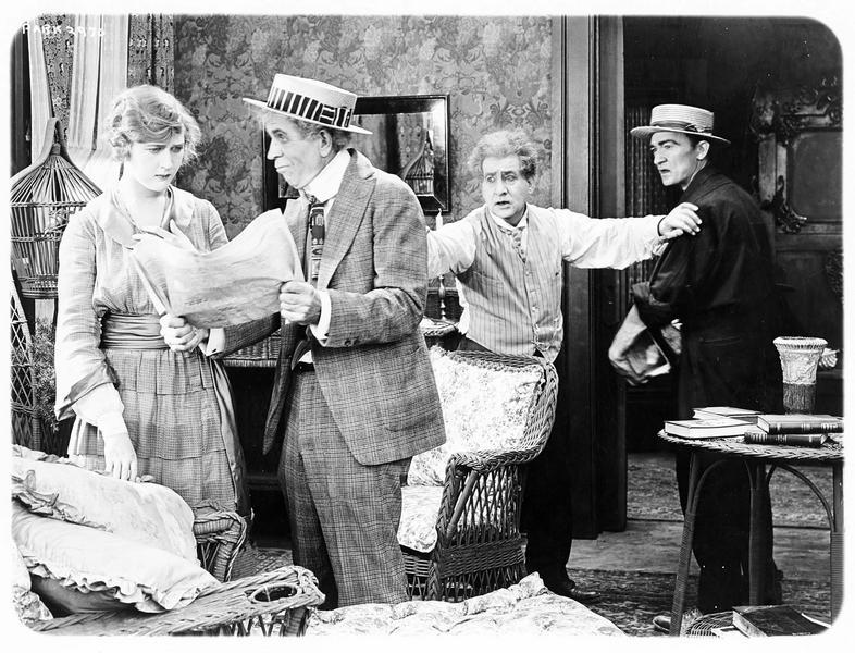 Un homme montrant le journal à une femme (M. MacLaren) à l'air stupéfait