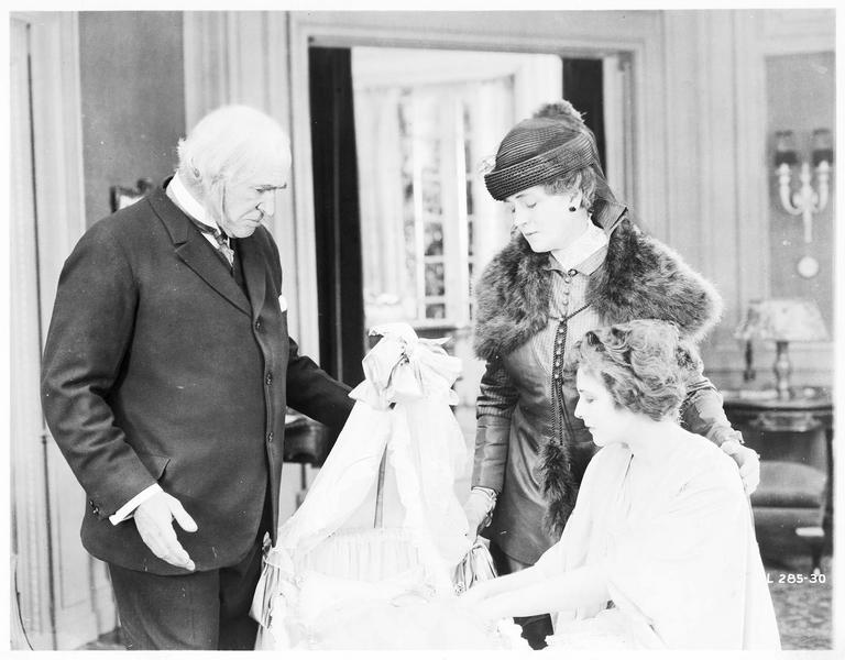 Mary MacNeill (K. MacDonald), Daniel MacNeill (T. Roberts) et une dame autour du berceau