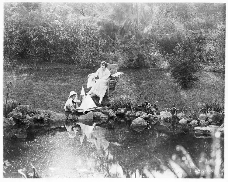 Mary MacNeill (K. MacDonald) au bord d'un étang avec un enfant
