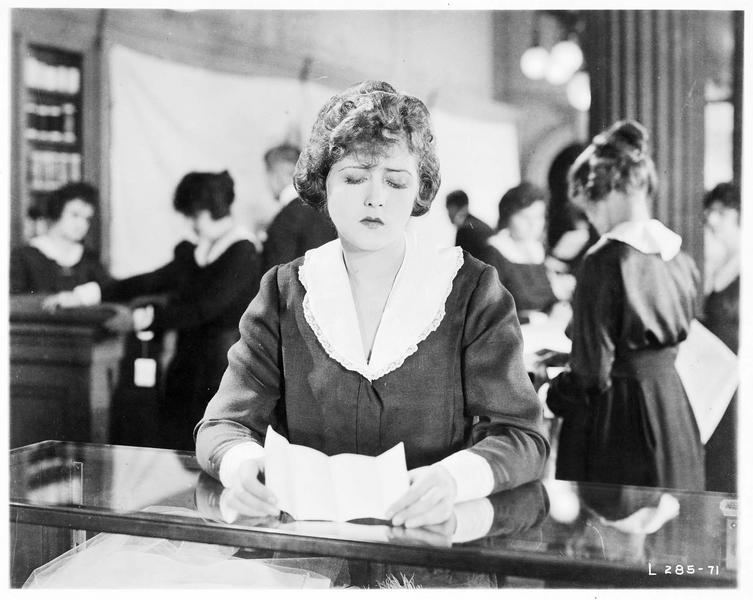 Mary MacNeill (K. MacDonald) lisant un billet