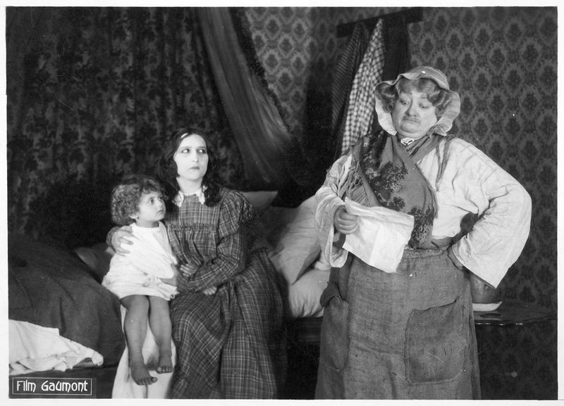 La mère Moscou (M. Guitty) et une jeune femme (I. Sabel) tenant un enfant sur les genoux