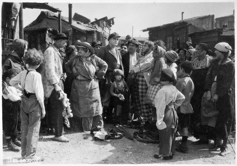 La mère Moscou (M. Guitty) réunissant la foule autour d'elle dans la rue d'un bidonville