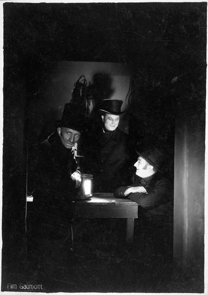 Trois hommes réunis autour d'une petite table
