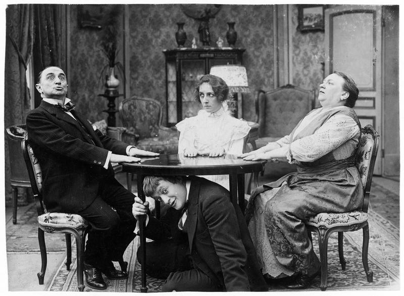 Picroche (L. Maurel) et sa femme (M. Guitty) s'adonnant à une séance de spiritisme tandis que Plouf (F. Morel) se cache sous la table