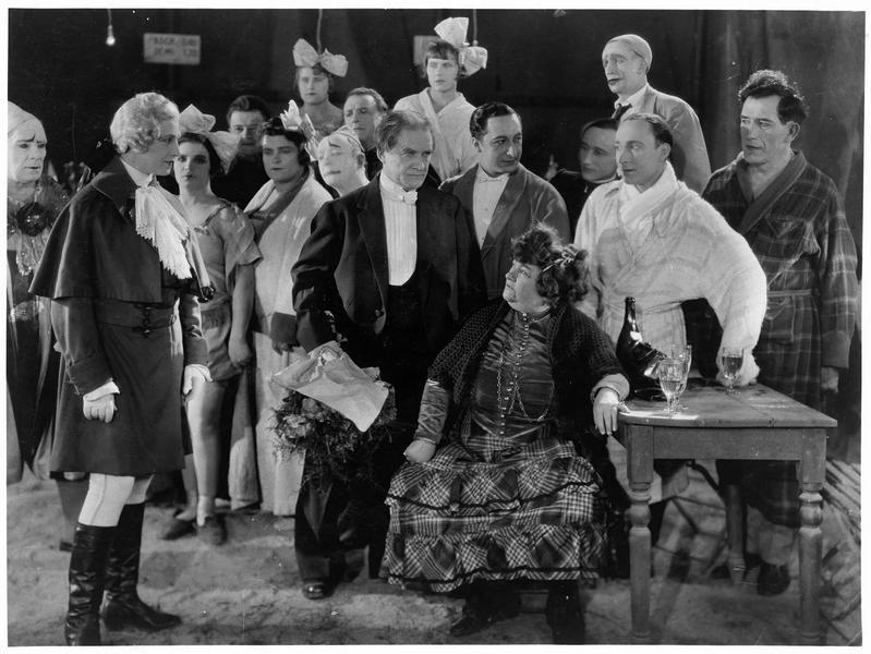 Une femme (M. Guitty) entourée de personnes costumées
