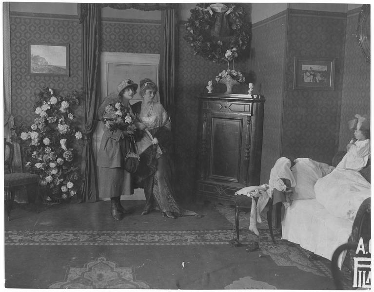 Deux jeunes femmes regardant une fillette debout sur le canapé