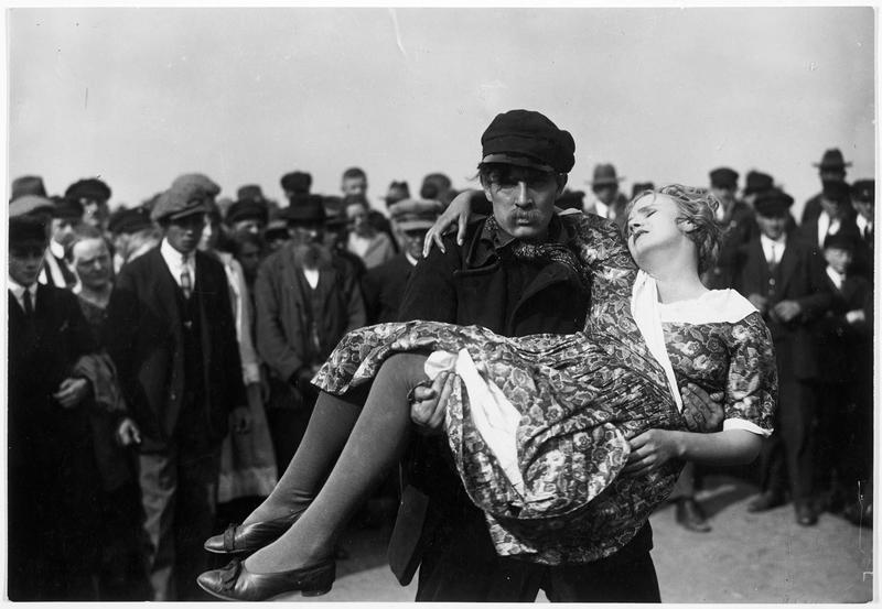 Un homme (H. Stüwe) portant une jeune femme évanouie (M. Delschaft)